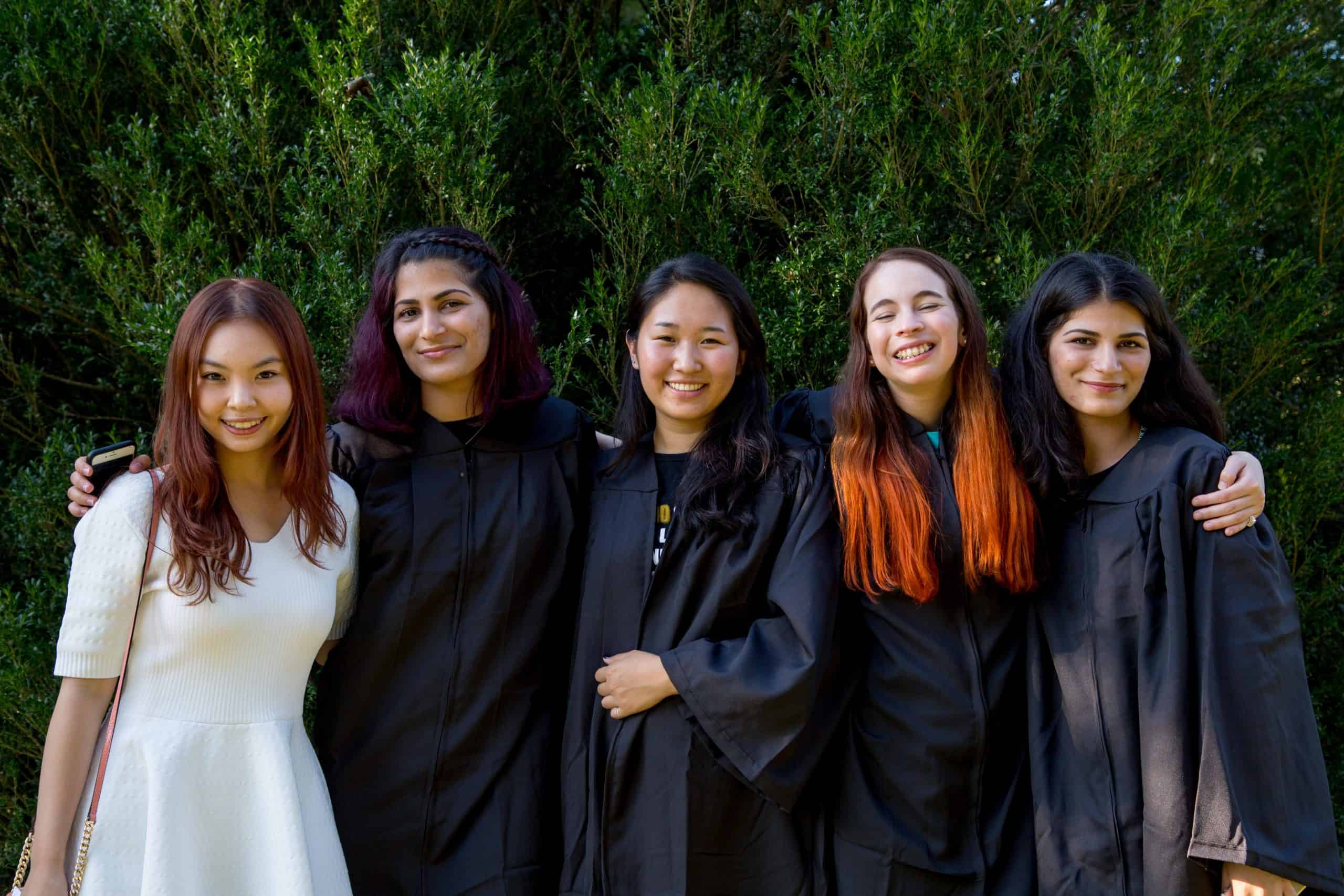 A group of five students wearing graduation robes pose