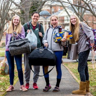 Four students moving into a residence hall