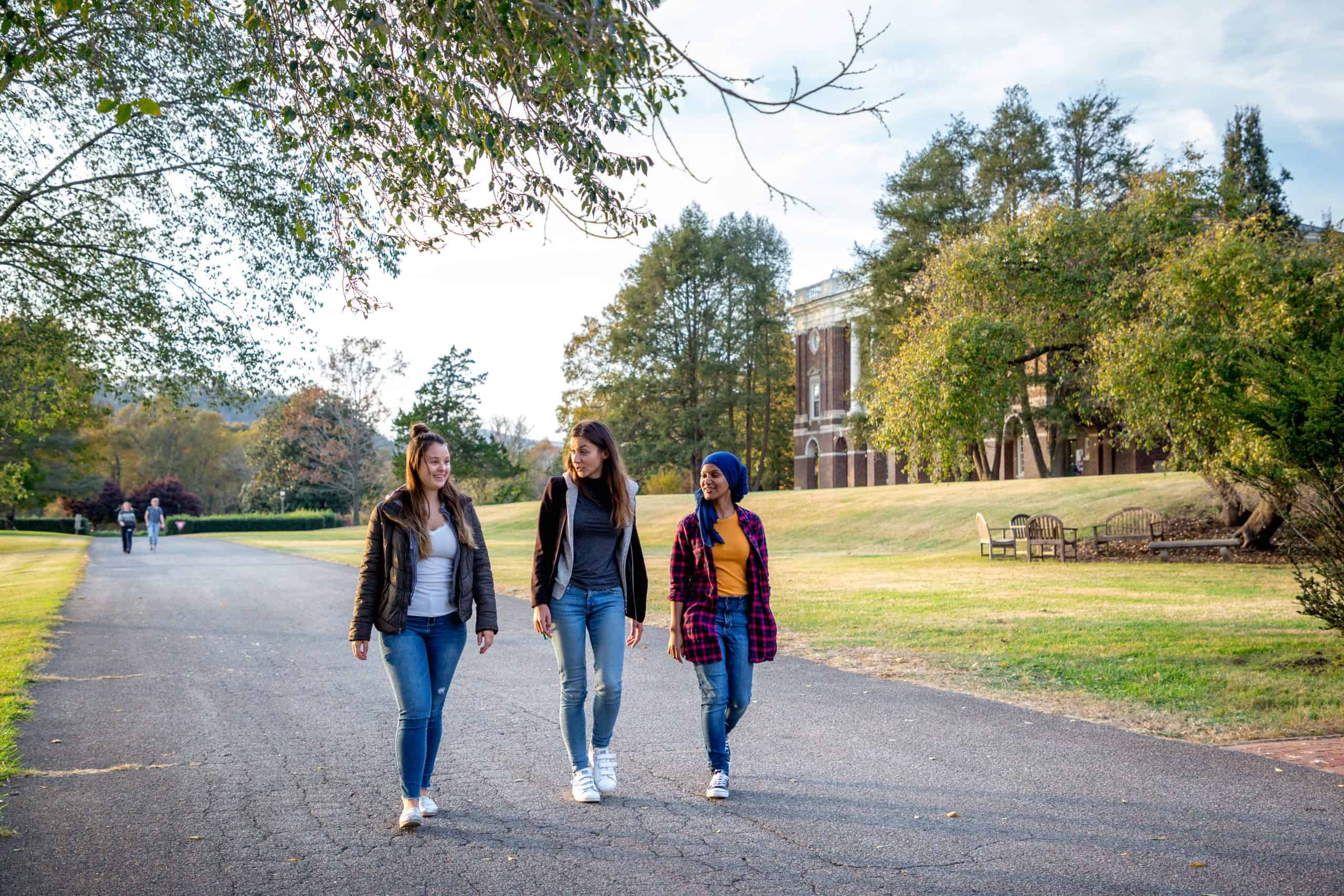Three female students walk down a road with a building in the background