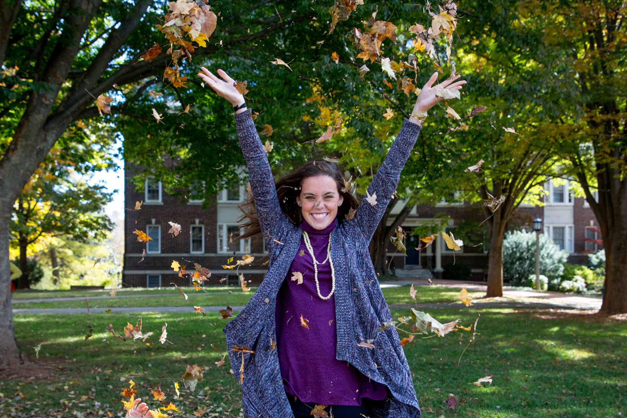 A female student throws leaves into the air