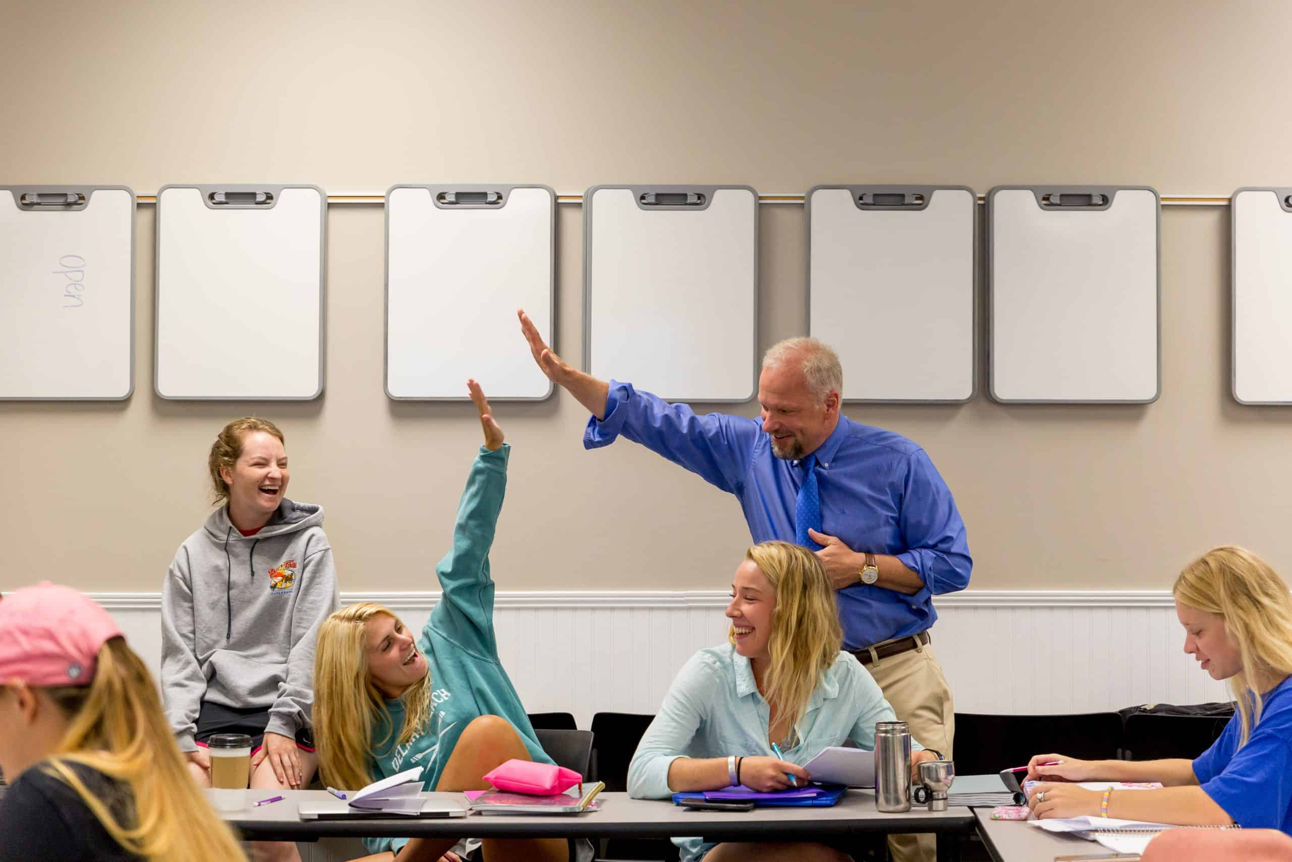 Professor high-fiving a student