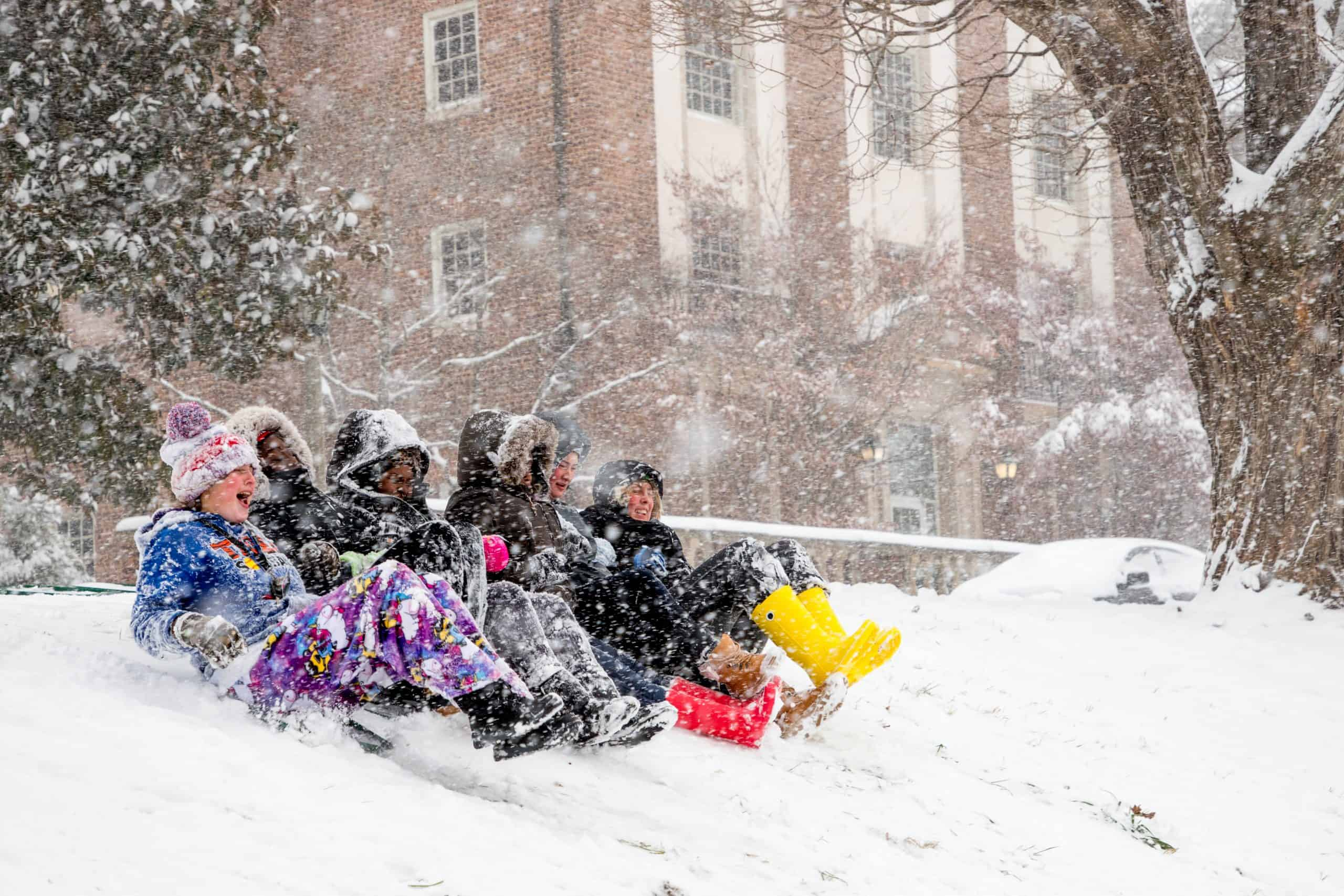 Students sledding down a hill in the snow