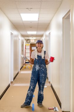 An alumna poses while painting a hallway
