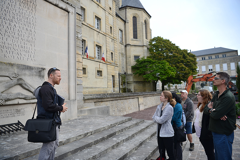 Geert van den Bogaert, a professional D-Day guide, addresses the group at the Bayeux memorial to local victims of fascism.