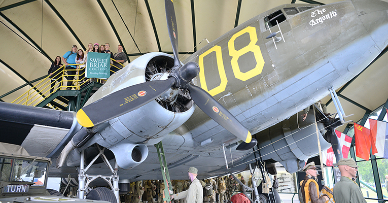 The group stands above a C-47 cargo plane that was used in the Allied invasion.