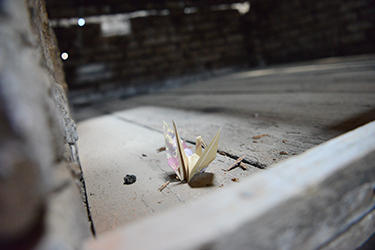 An origami crane on the bunks of one of the women's barracks at Auschwitz