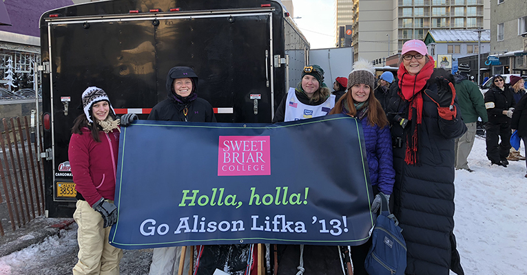 Alison Lifka and fellow alumnae with banner