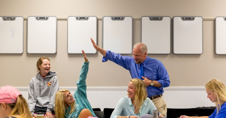 A Sweet Briar professor high fives a student in class