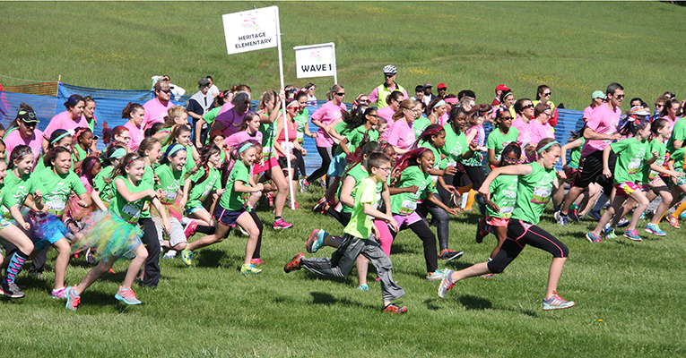 A pink-and-green wave goes in motion as runners start the 2015 spring Celebration 5K.