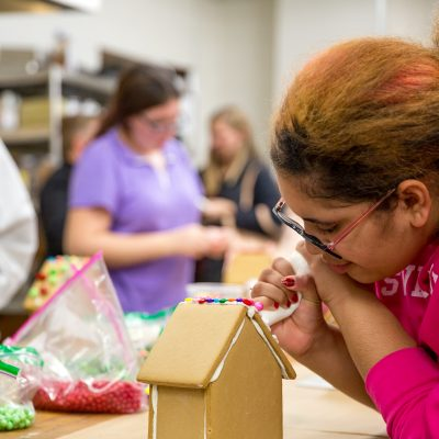 First year, Brianna Rabassa decorates a gingerbread house.