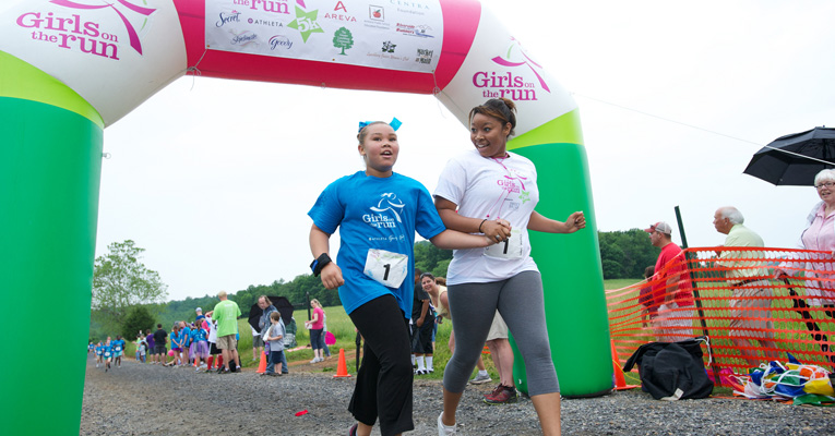 A runner culminates 12 weeks of training and learning in the Girls on the Run program as she crosses the finish line with her running buddy.