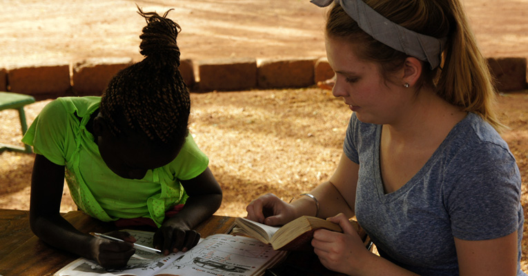 Holly Rueger '17 (right) at the orphanage helping Pauline with her homework