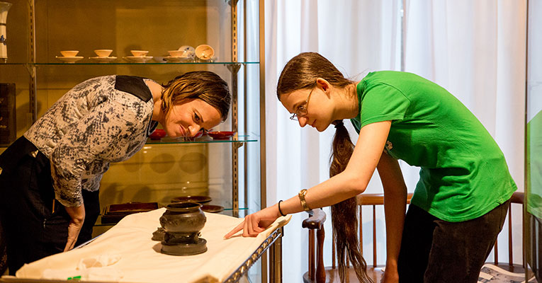 Jessie Meager '18 and her Honors Summer Research faculty sponsor, Prof. Kimberly Morse-Jones, inspect a Japonisme artifact in Sweet Briar College's museum collection.