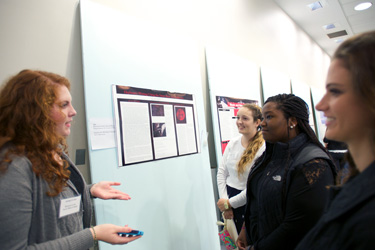 Khirsten Cook '15 (left) talks about her ekphrasis writing project and novel with conference attendees.