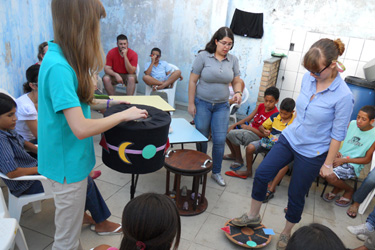 Kate Fanta '15 and Kiera Cavalleri '15 demonstrate a vestibular therapy game designed for children with autism or other sensory input disorders at an occupational therapy clinic in lhéus, Brazil.