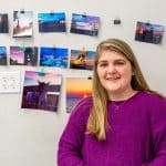 Lashlee McCray smiling in front of her photographs