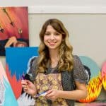 Amelia Mendelsohn holding a paintbrush with her artwork