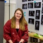 Katherine Martin smiling with her photos for her art project